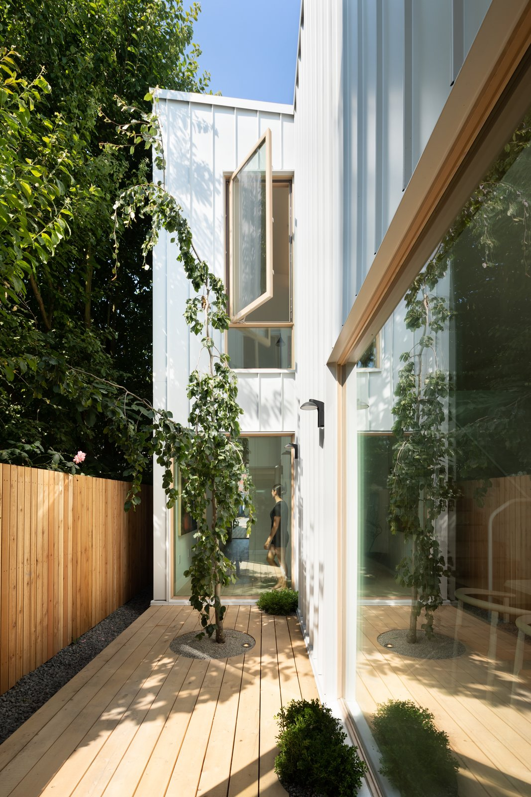 Outdoor, Vertical Fences, Wall, Walkways, Small Patio, Porch, Deck, and Side Yard A courtyard in the mid-section of the house draws plenty of light to its center.     Best Photos from 11 Skylights Brighten a Compact, Narrow Home in Vancouver
