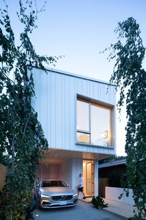 The clean lines of the house's minimalist façade is accented by standing-seam metal cladding.