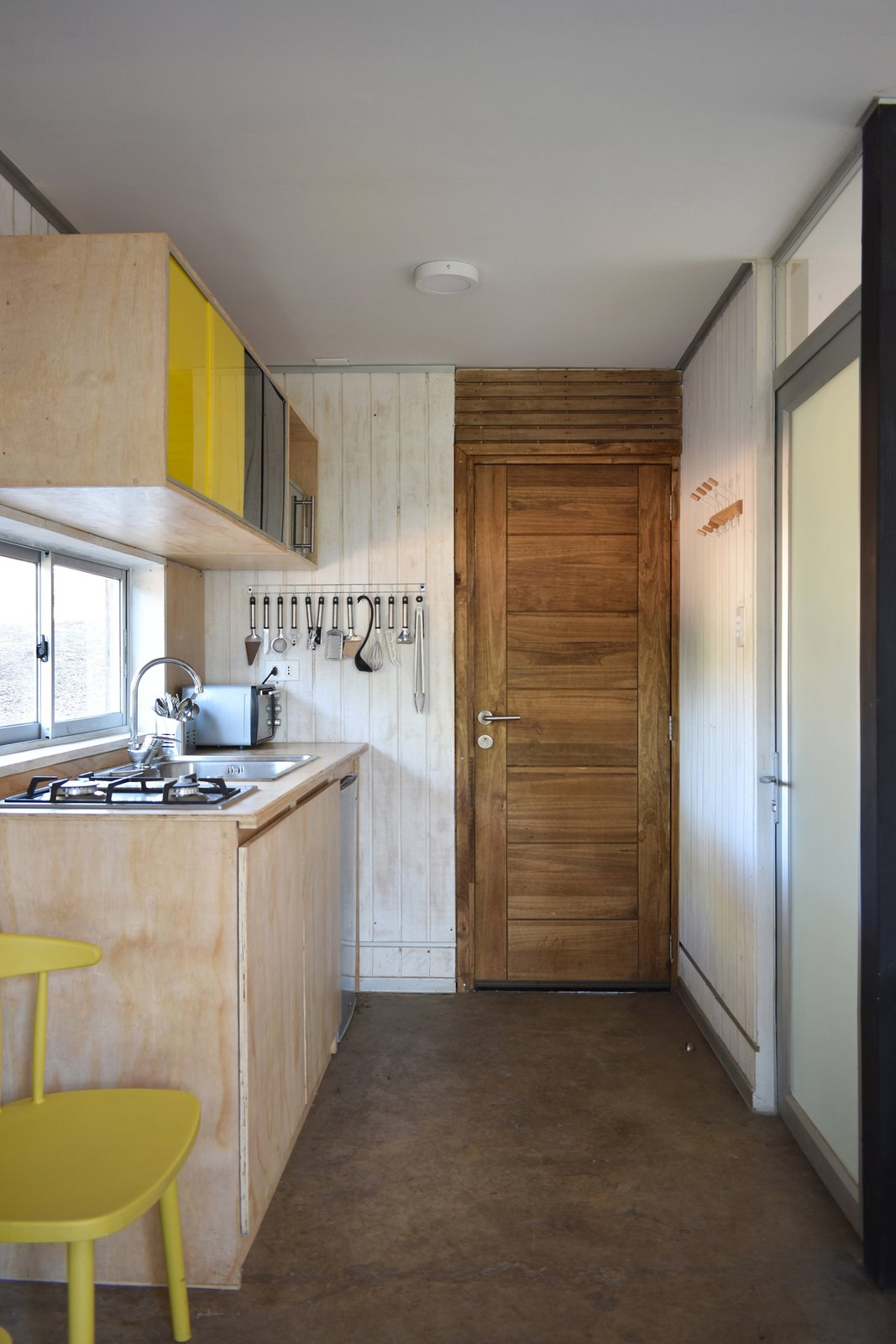 Kitchen, Drop In Sink, Ceiling Lighting, Cooktops, Wood Counter, Wood Cabinet, and Refrigerator The kitchen area and living/dining spaces are located on the first level, along with a bathroom.  Best Photos from A Patagonian Prefab Cabin Is Built to Withstand Volatile Climates