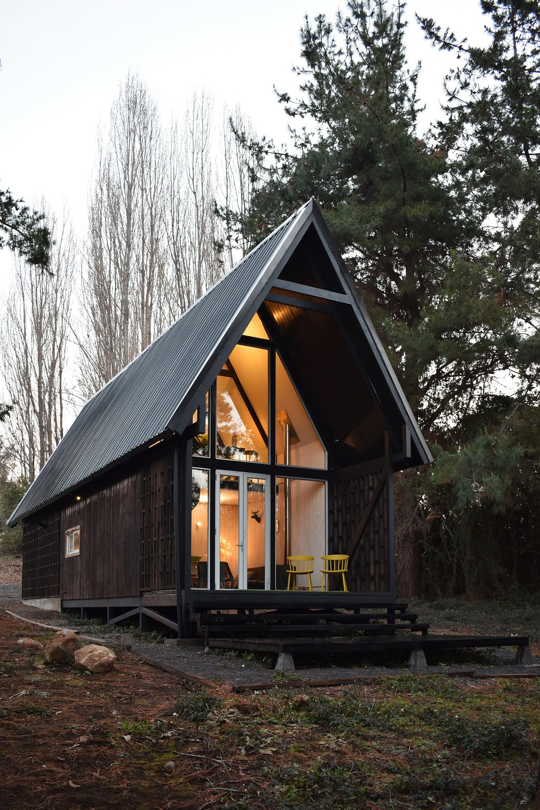 Exterior, A-Frame RoofLine, Prefab Building Type, Small Home Building Type, House Building Type, Wood Siding Material, Metal Roof Material, and Cabin Building Type The chiflonera leads to the entrance of the cabin.  Best Photos from A Patagonian Prefab Cabin Is Built to Withstand Volatile Climates