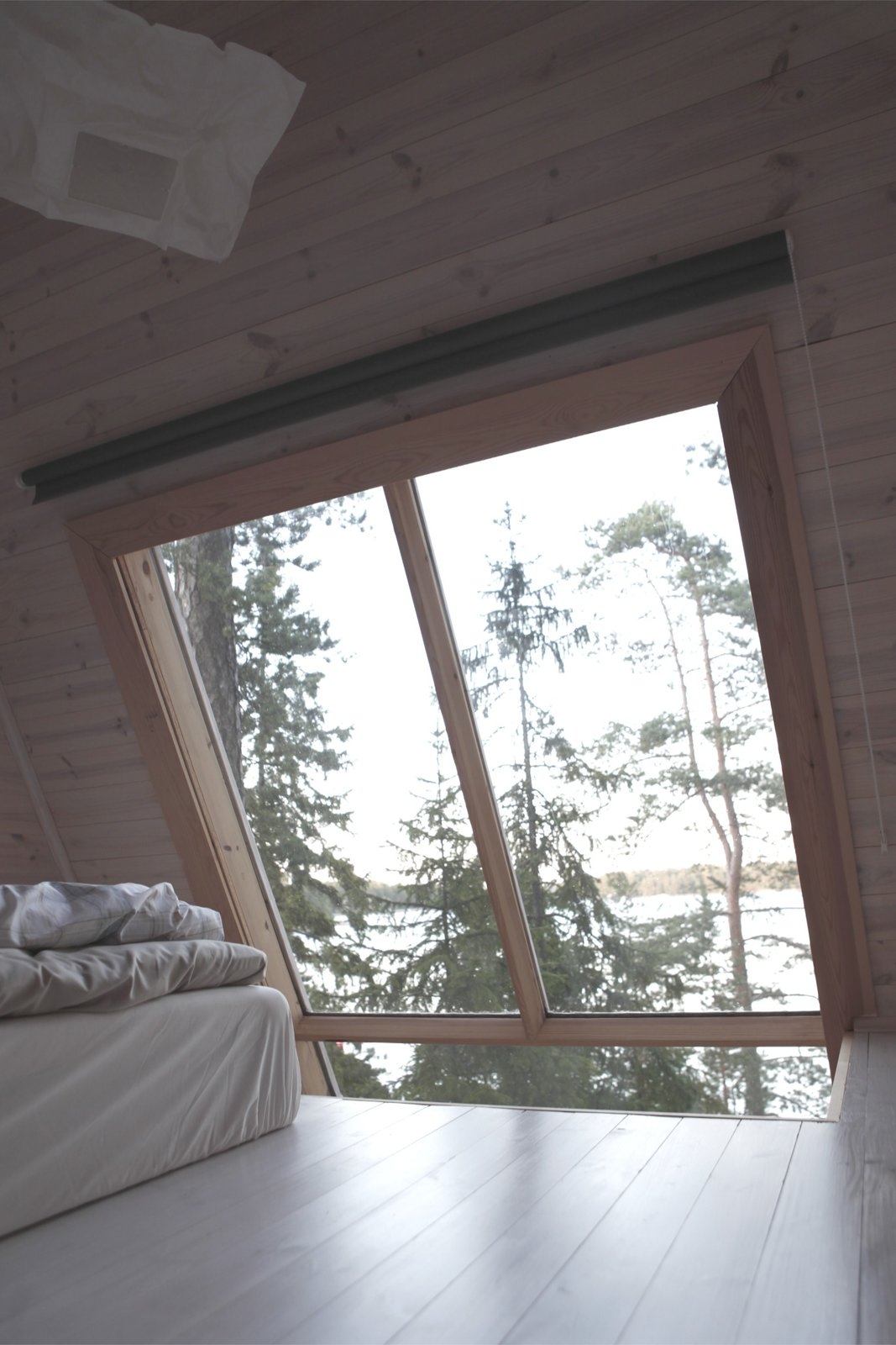 Nido Tiny Cabin by Robert Falck indoor view from top floor loft bedroom with light wood flooring and walls with large three panel window framed with wood