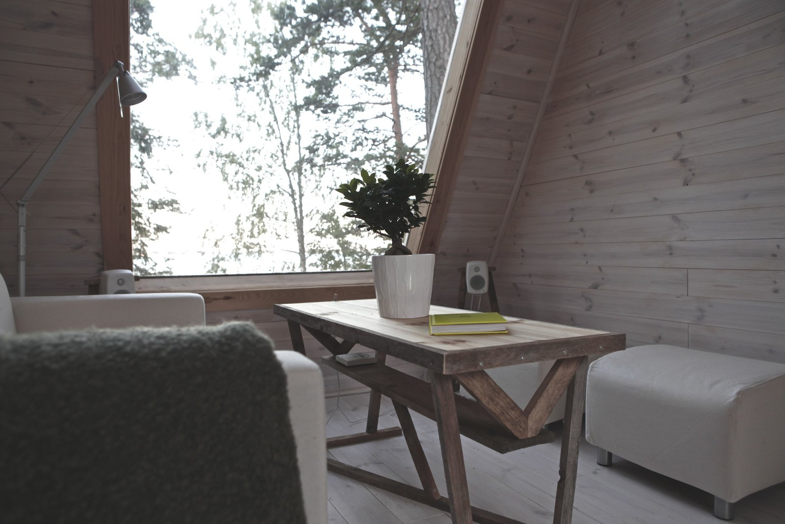 Nido Tiny Cabin by Robert Falck living room with cream colored sofa and ottomans, rustic wood coffee table and light wood walls and floors.