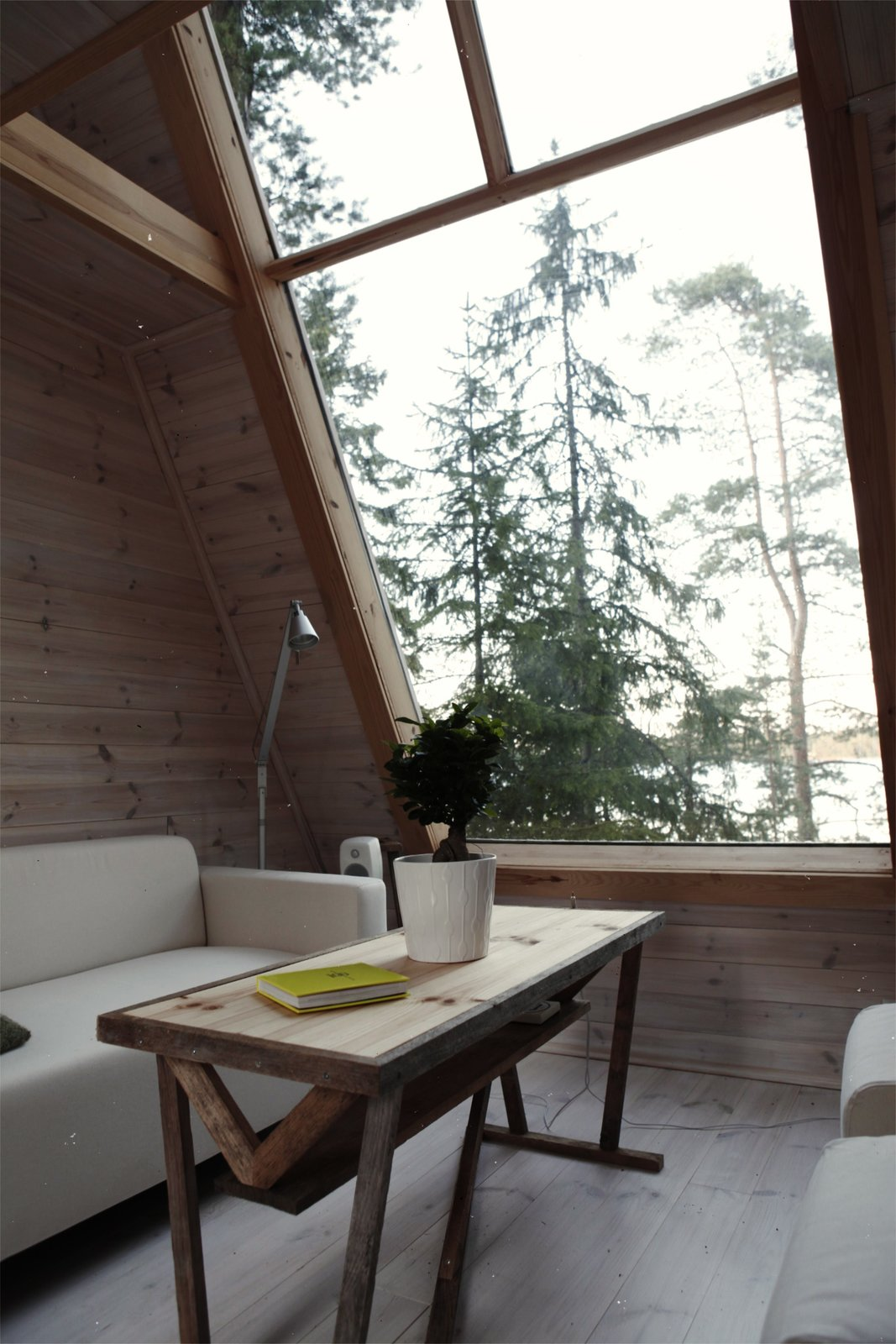 Nido Tiny Cabin by Robert Falck living room with cream sofa and ottomans, wood coffee table, wood walls and floors and large three panel window framed in wood
