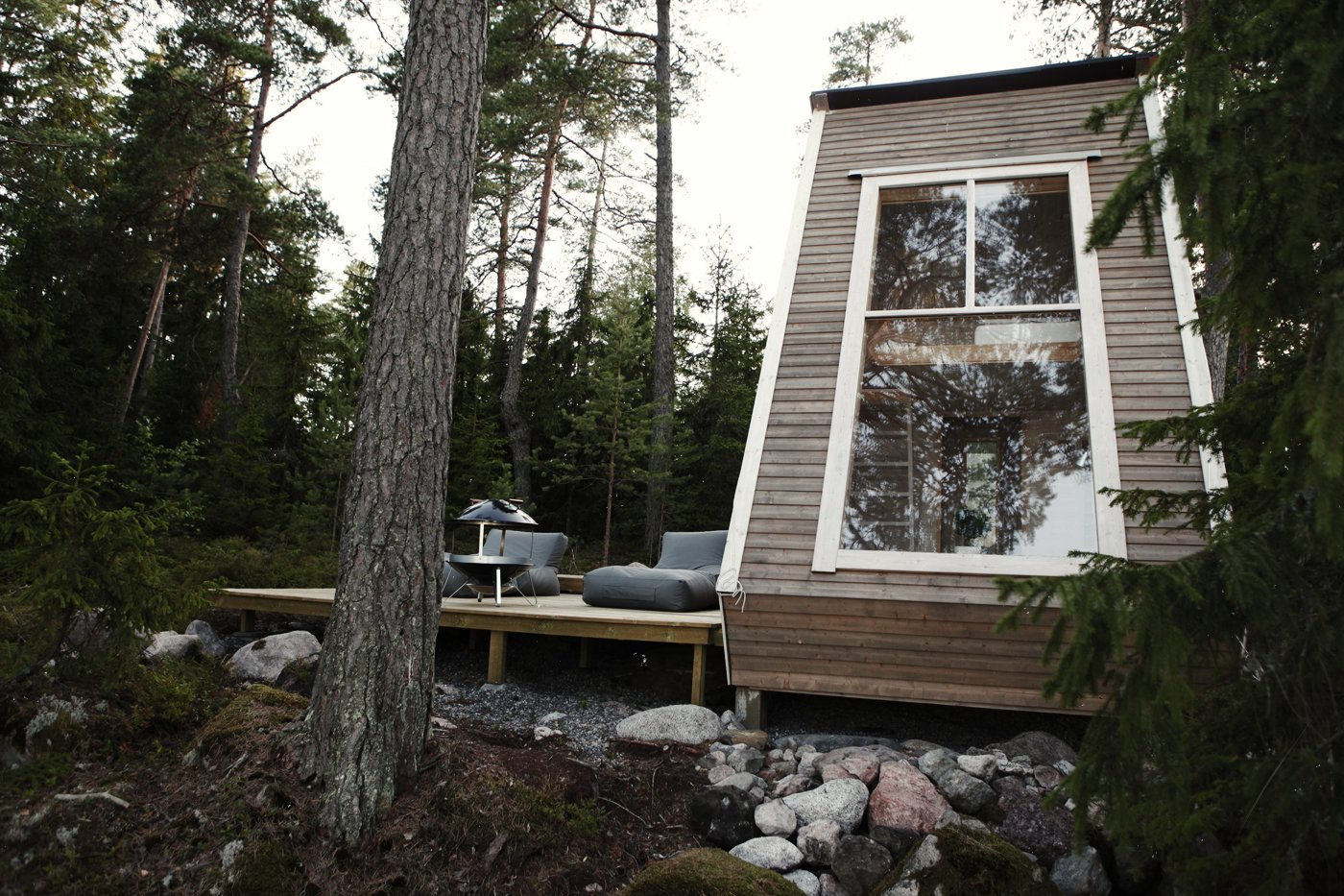 Nido Tiny Cabin by Robert Falck exterior with three panel window and recycled wood deck patio in Sipoo forest in Finland