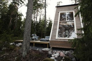 Adjacent to the cabin is a spacious deck that is raised above the ground on wooden stilts.