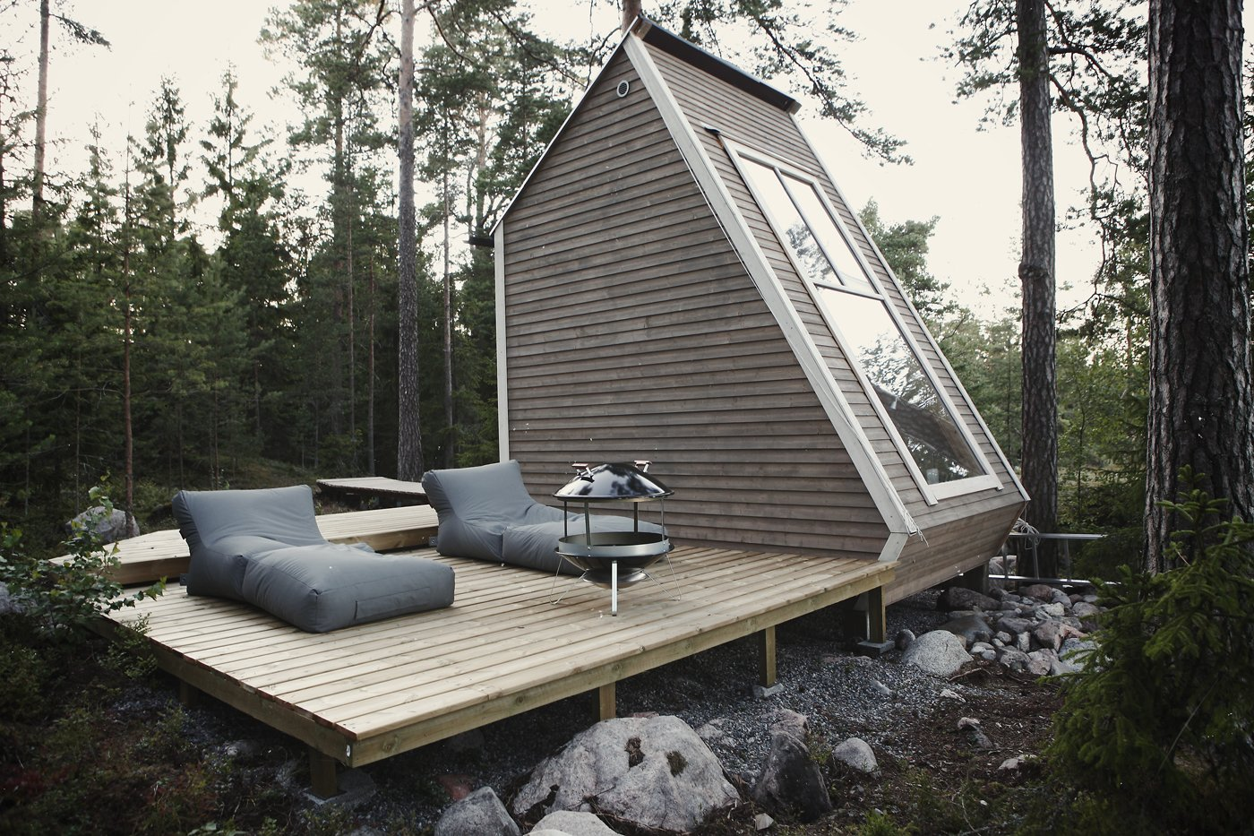 Nido Cabin by Robert Falck exterior with wood deck patio and forest landscape