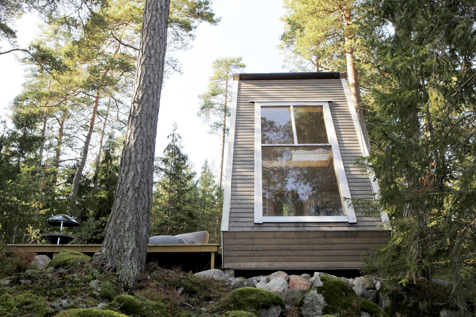 Nido Tiny Cabin by Robert Falck exterior three panel window with white siding in forest landscape
