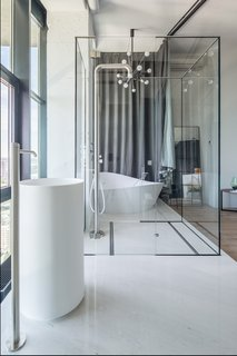 A glass wall separates the ensuite bathroom from the bedroom, allowing additional natural light to flood the space. A curtain can be drawn along this wall when privacy is needed.