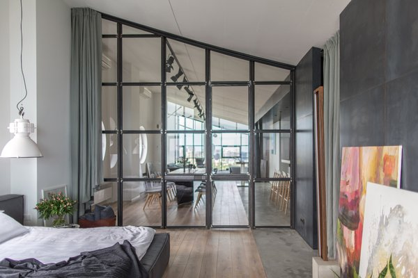 The entrance to the master bedroom is through a sloped wall of framed windows.