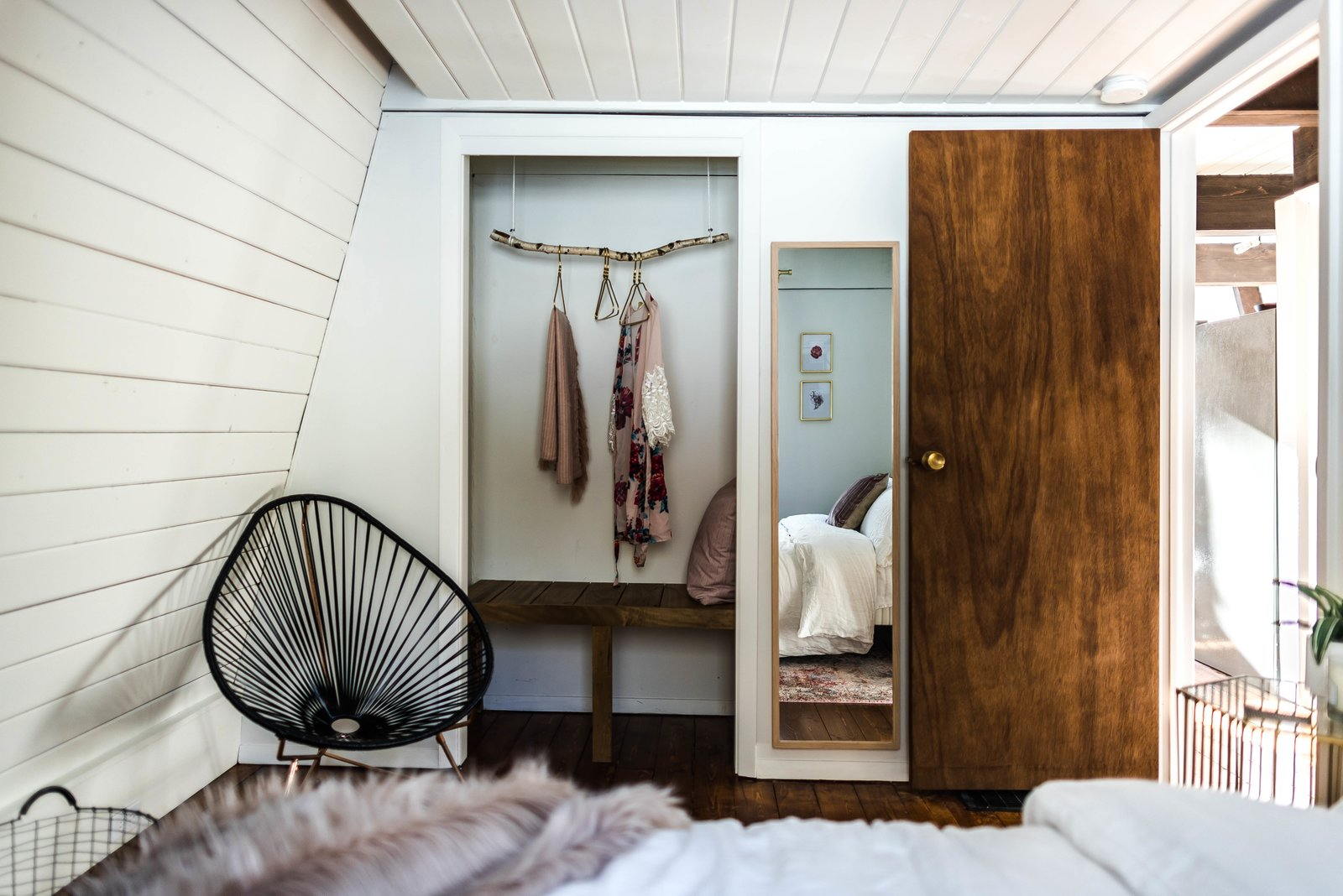 Bedroom, Bed, Wardrobe, Dark Hardwood Floor, and Chair Once the tiling, grouting and painting were gone, they began having fun with the design, layout, and furnishing.  Photo 20 of 26 in Budget Breakdown: Weekend DIYers Renovate a Dated Catskills Retreat For $201K
