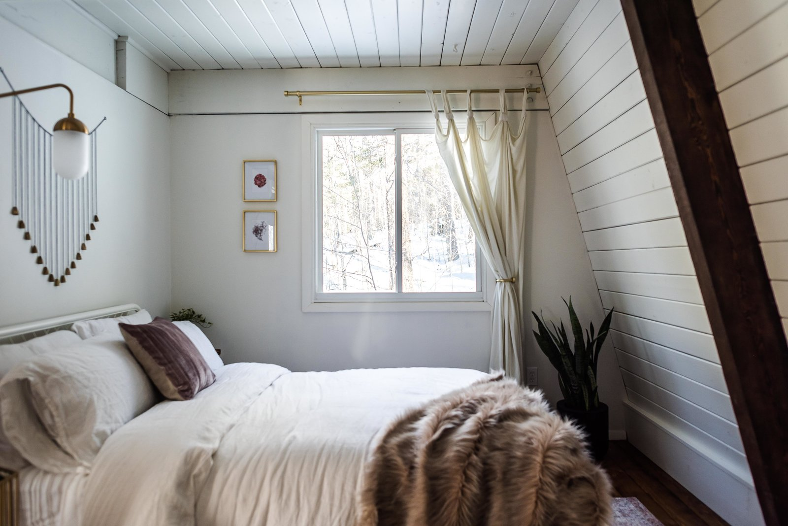 Bedroom, Dark Hardwood Floor, Bed, and Wall Lighting Carefully selected textiles and potted plants give the rooms a warm and cozy feel.  Photo 23 of 26 in Budget Breakdown: Weekend DIYers Renovate a Dated Catskills Retreat For $201K