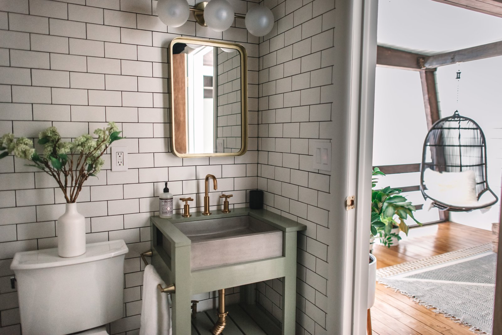 Bath Room, Two Piece Toilet, Subway Tile Wall, Wall Lighting, and Pedestal Sink A guest bathroom is located near the top of the stairs.  Photo 26 of 26 in Budget Breakdown: Weekend DIYers Renovate a Dated Catskills Retreat For $201K