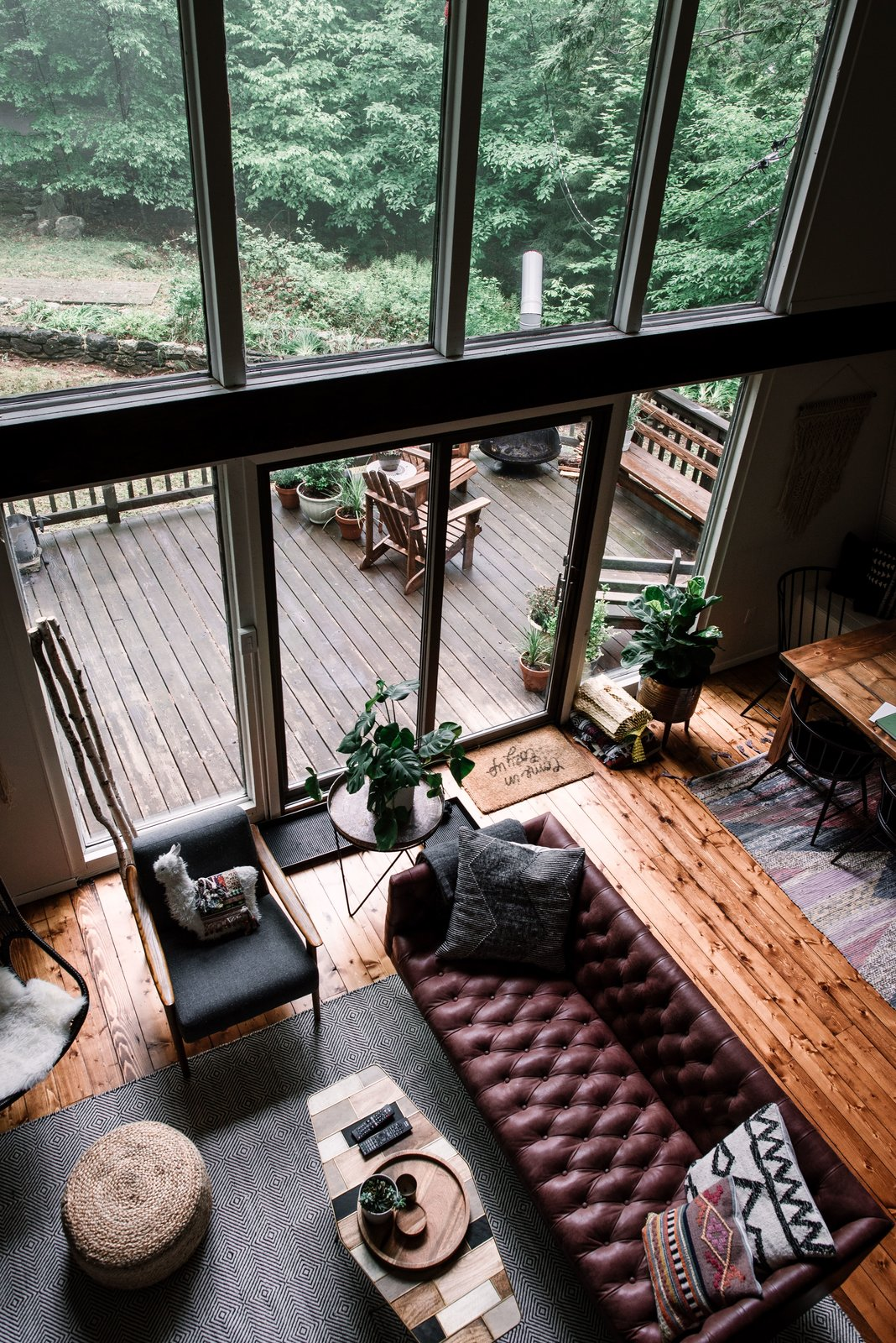 Living Room, Sofa, Coffee Tables, End Tables, Ottomans, Medium Hardwood Floor, and Chair The living and dining area opens out to a spacious raised deck.  Photo 11 of 26 in Budget Breakdown: Weekend DIYers Renovate a Dated Catskills Retreat For $201K