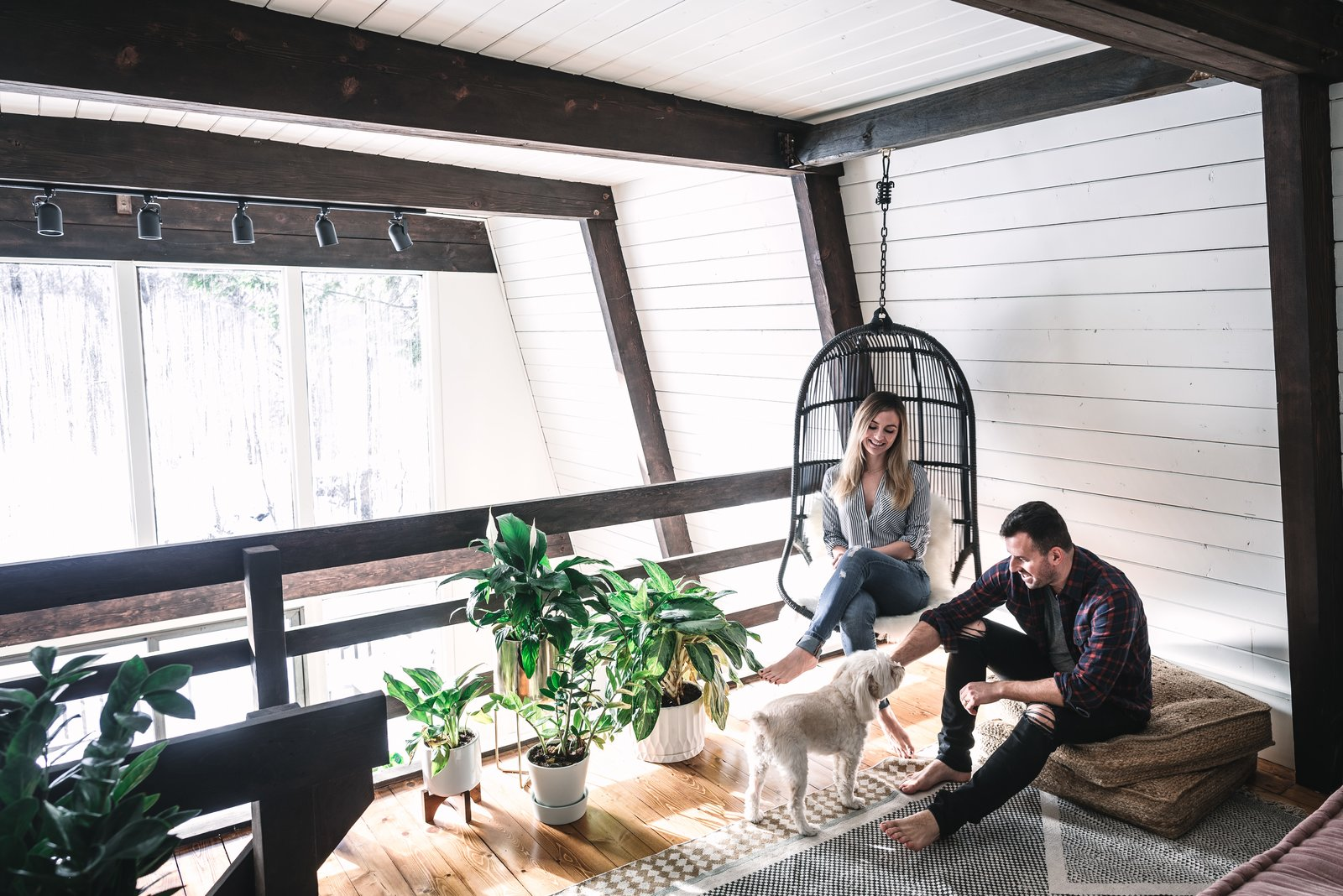 Living Room, Chair, Medium Hardwood Floor, and Track Lighting Danielle and Ely Franko relax with their pooch in the loft area.  Photo 18 of 26 in Budget Breakdown: Weekend DIYers Renovate a Dated Catskills Retreat For $201K