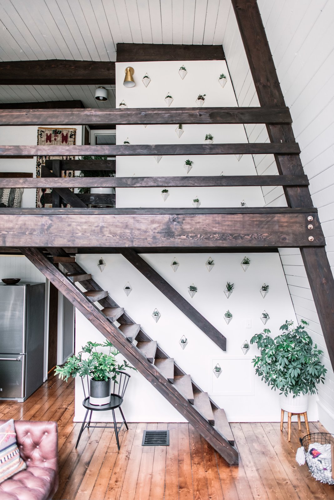Staircase, Wood Tread, and Wood Railing From the living lounge, wooden stairs lead up to the bedrooms.  Photo 19 of 26 in Budget Breakdown: Weekend DIYers Renovate a Dated Catskills Retreat For $201K