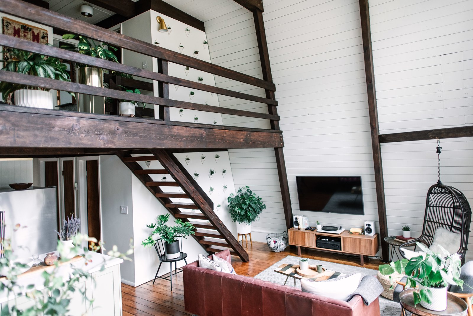 Living Room, Coffee Tables, Medium Hardwood Floor, Chair, Bench, End Tables, and Wall Lighting The fresh, white interiors help the home feel more spacious and offset the exposed wood beams.  Photo 10 of 26 in Budget Breakdown: Weekend DIYers Renovate a Dated Catskills Retreat For $201K