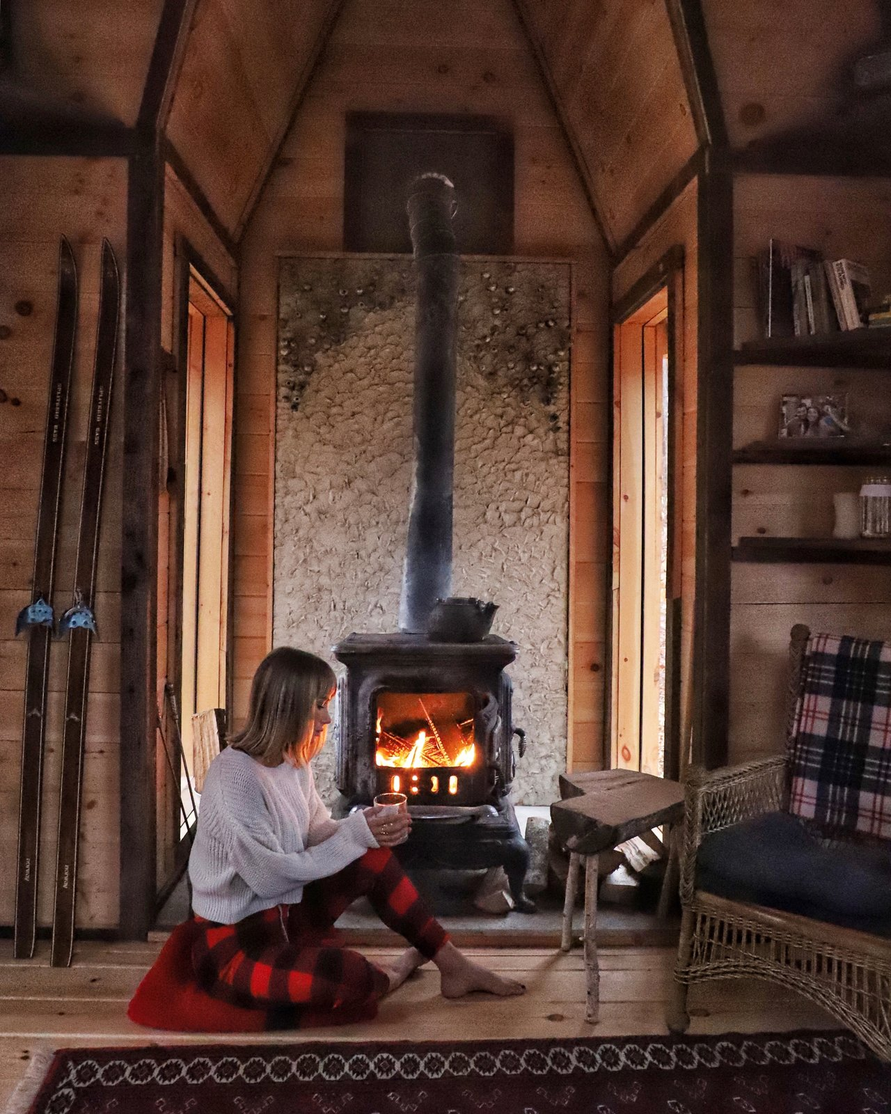 Living Room, Wood Burning Fireplace, Light Hardwood Floor, and Chair Sara Underwood relaxes by the fireplace in Witzling's fifth cabin.  Photo 3 of 21 in Jacob Witzling's Off-Grid Cabins Are Straight Out of a Fairy Tale