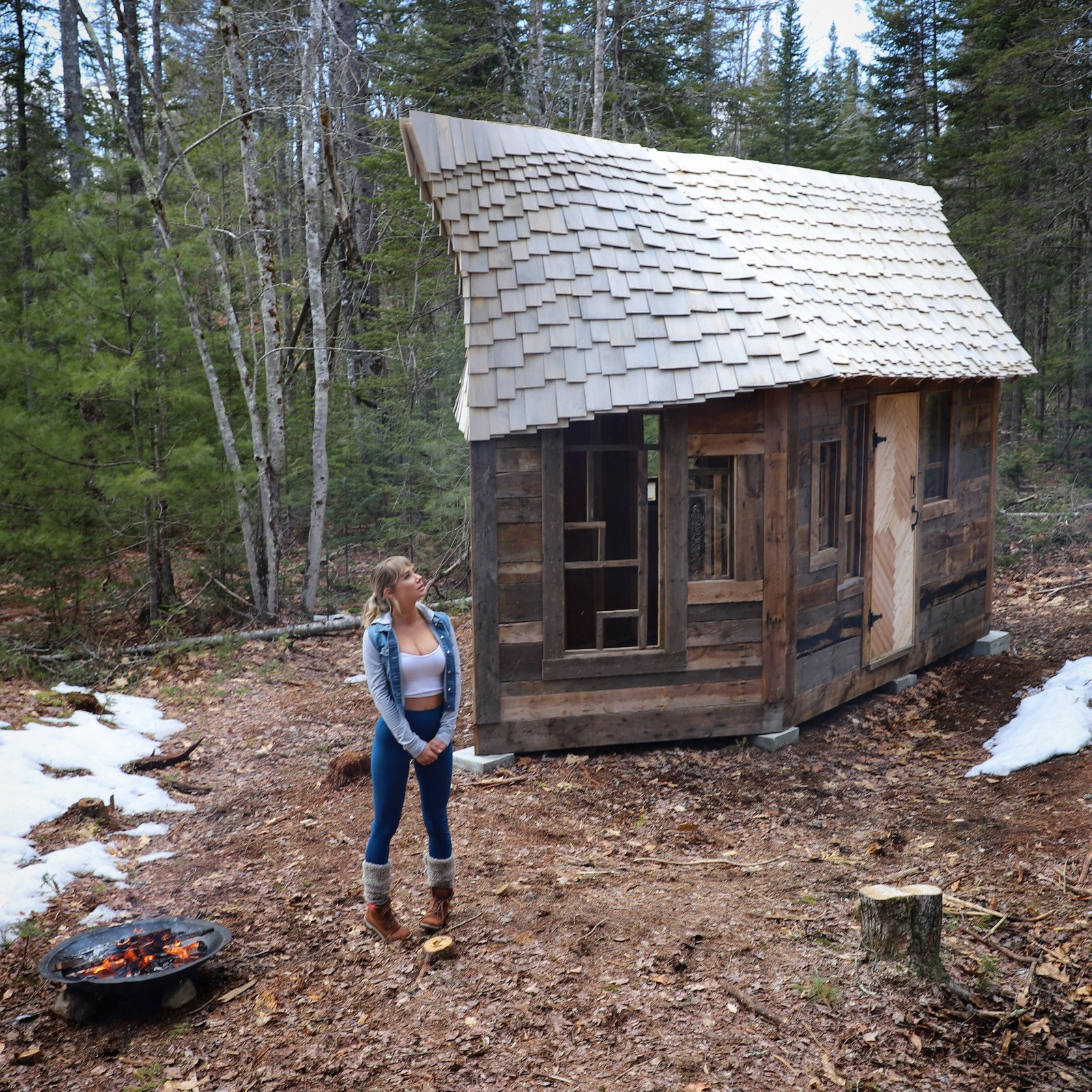 Exterior, Shingles Roof Material, Cabin Building Type, Wood Siding Material, and Tiny Home Building Type Witzling's life partner, model and actress Sara Underwood, explores Cabin 4.  Photo 16 of 21 in Jacob Witzling's Off-Grid Cabins Are Straight Out of a Fairy Tale