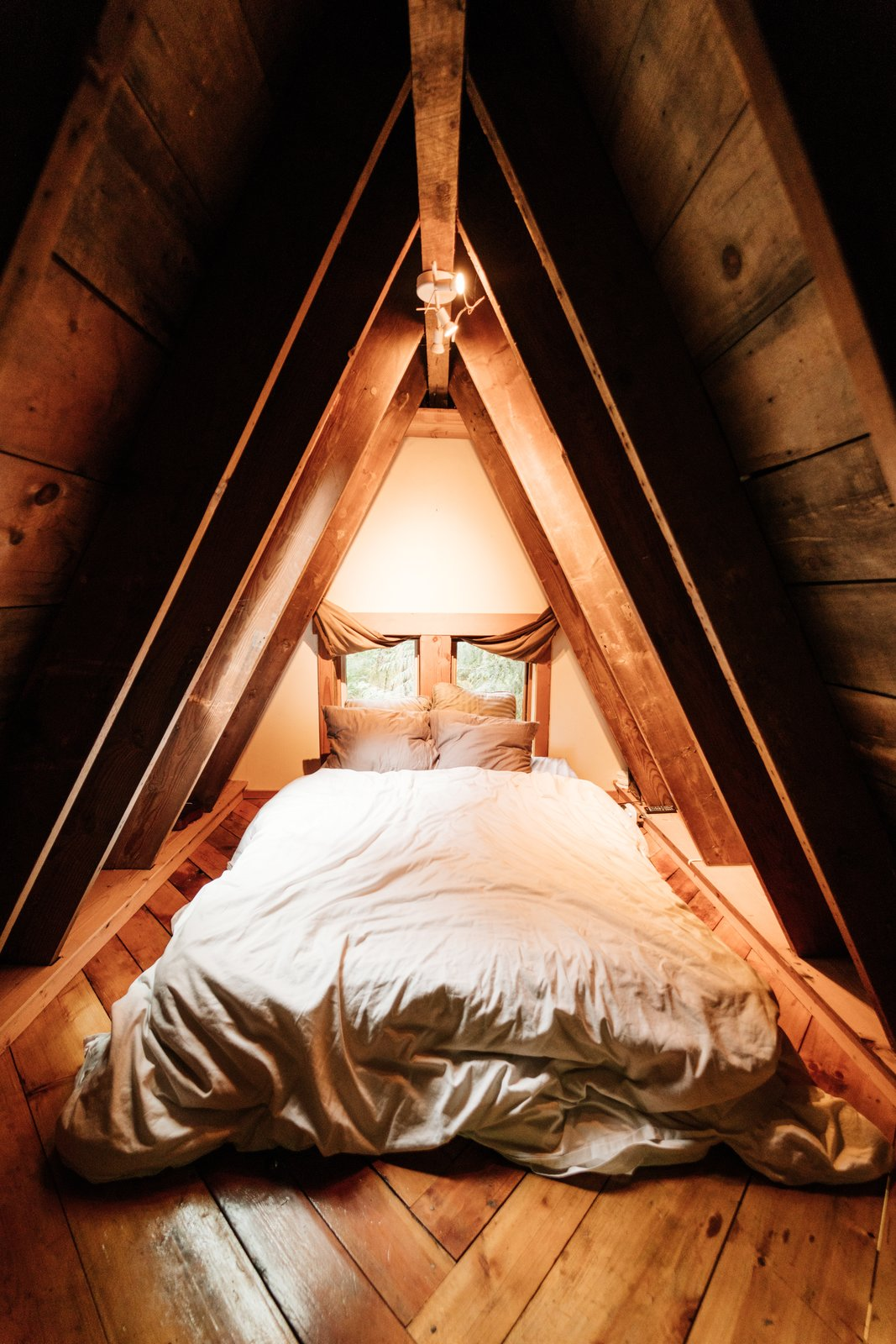 Bedroom, Bed, Ceiling Lighting, and Medium Hardwood Floor It has two ridges that intersect perpendicularly.  Photo 13 of 21 in Jacob Witzling's Off-Grid Cabins Are Straight Out of a Fairy Tale