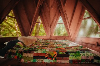 An octagonal cabin boasts a lofted sleeping area with views of the forest outside.