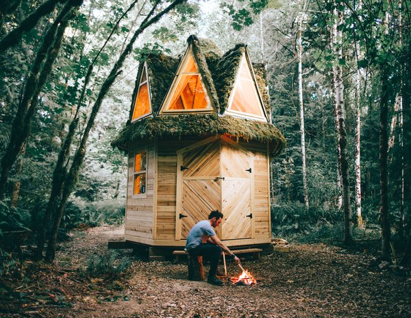 """""""I get my design inspiration from cabins of the past, from the world of fantasy both in movies and books, and in that childlike part of my imagination that I'm continually trying to preserve,"""" says designer and builder Jacob Witzling, who crafts one-of-a-kind tiny homes, using  salvaged scraps from local lumber mills and building sites, as well as materials found in nature. Witzling's design for a 135-square-foot cabin with an octagonal base and an octagonal pyramid roof was built with plenty of help from his lifelong friend Wesley Daughenbaugh. Each of the designer's creations are built off the electric grid, instead powered by a 12-volt D/C system using deep cycle batteries. Drinking, cooking, and bathing water is collected from a well, and a composting toilet is located in a separate outhouse structure."""