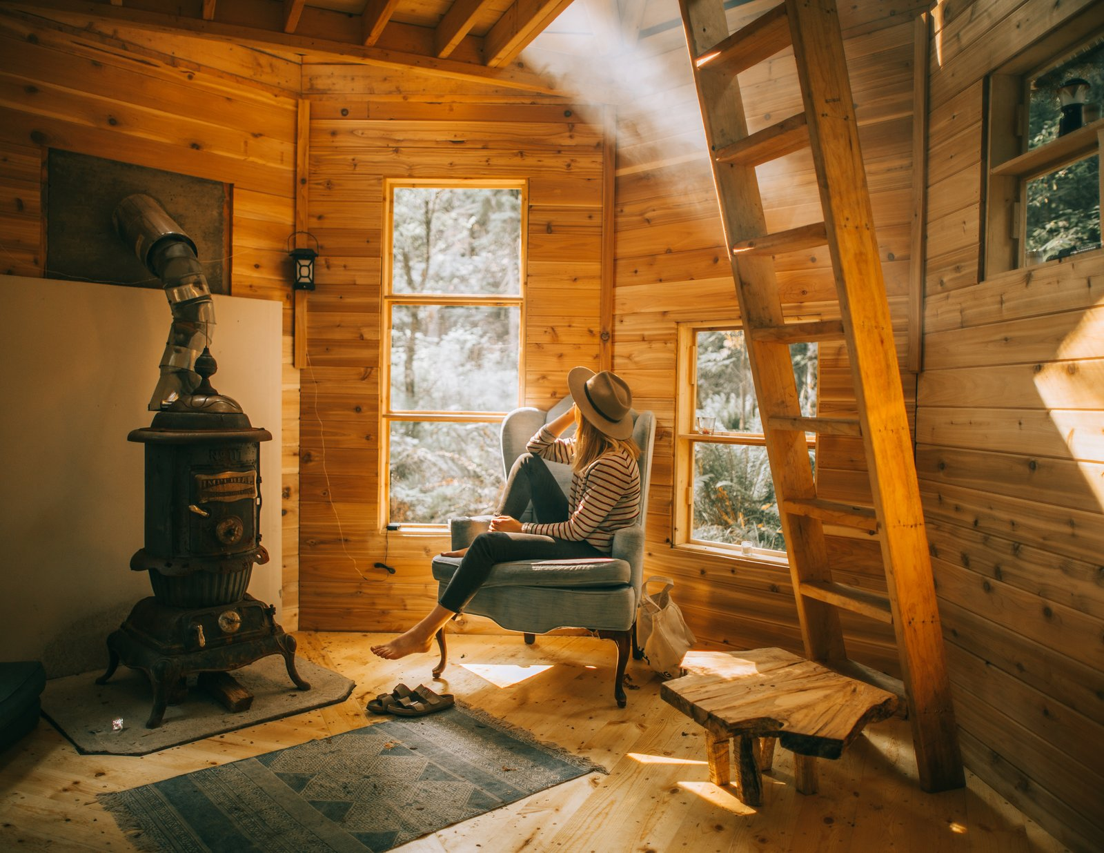 Living Room, Chair, Wood Burning Fireplace, and Coffee Tables A roof plane with a ridge protrudes to form eight 72-inch-tall dormers that run directly into the valleys.  Photo 15 of 21 in Jacob Witzling's Off-Grid Cabins Are Straight Out of a Fairy Tale