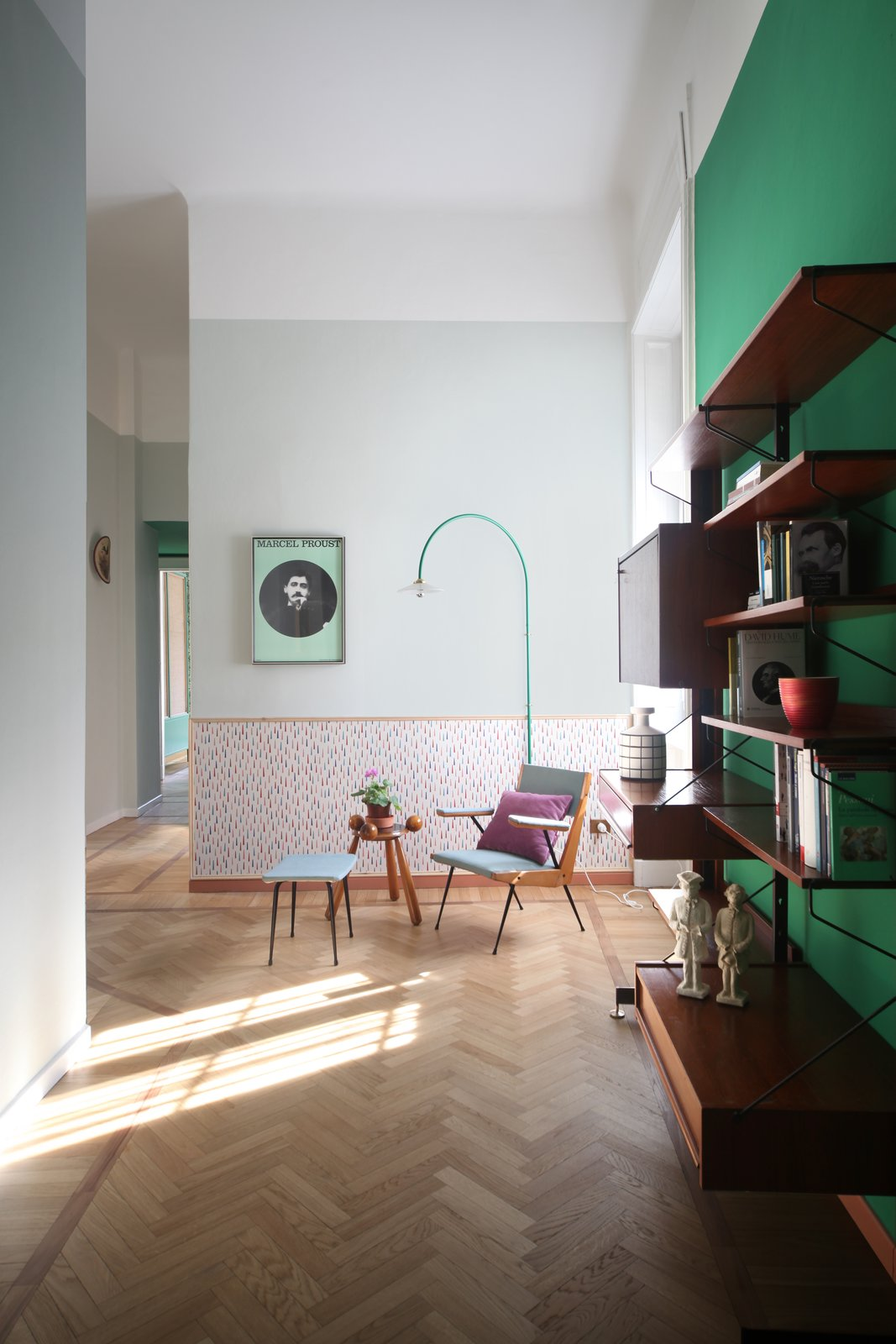 """Hallway and Medium Hardwood Floor Details of the passageway: wallpaper by Maharam, a reading area with a vintage bookcase, and a 1950s armchair from Carrozzeria 900.  Best Photos from This Delightful Abode Is a Modern Take on """"Grandma's House"""""""