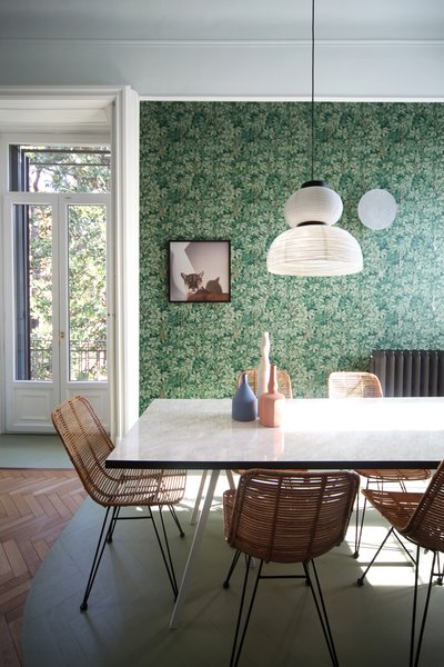 This room features wallpaper by Fornasetti for Cole&Son, a wall lamp Grillo by Petite Friture, a custom-made table-top in marble-effect laminate by Abet Laminati (sitting on legs by Hay), chairs by Hubsch, vases by Spotti, resin on parquet floor by Rezina, and a suspended lamp Formakami by &Tradition.