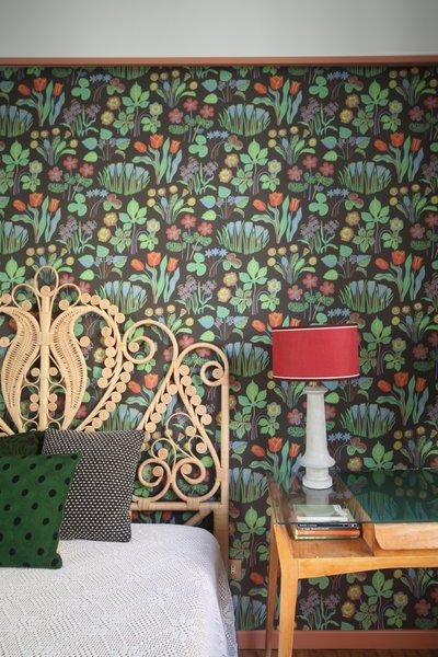 In this room, the wallpaper is by Svenskt Tenn, and the table lamp is by Servomuto.