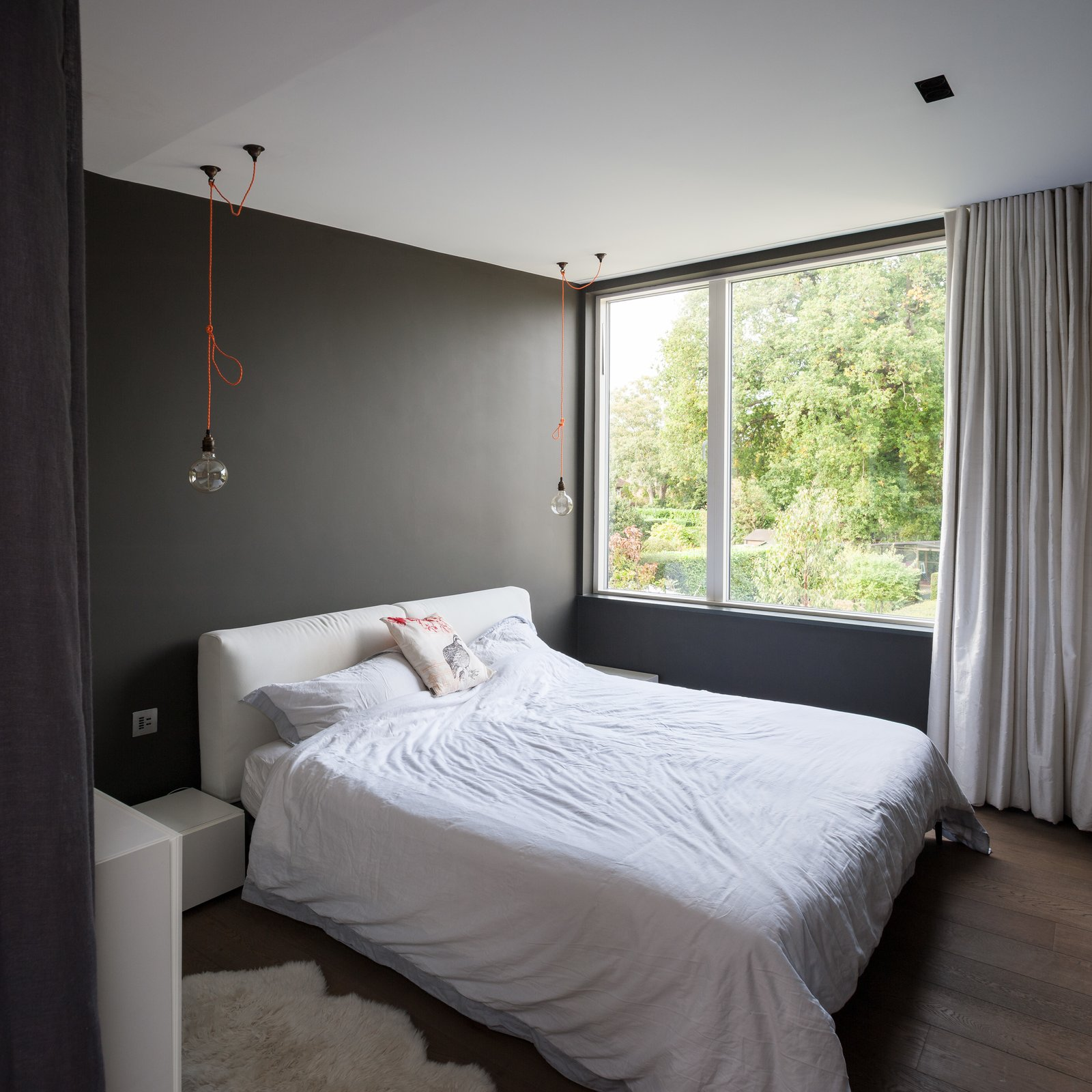 Bedroom with two hanging ceiling pendant bulb lights by each side of bed.