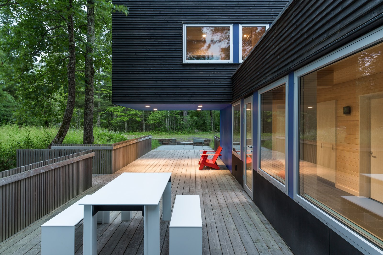 Outdoor, Shrubs, Grass, Large Patio, Porch, Deck, Trees, Wood Fences, Wall, and Vertical Fences, Wall The south-facing deck leads out to the sauna.  Best Photos from Two Rectangular Volumes Unite to Form a Colorful Lakeside Cabin