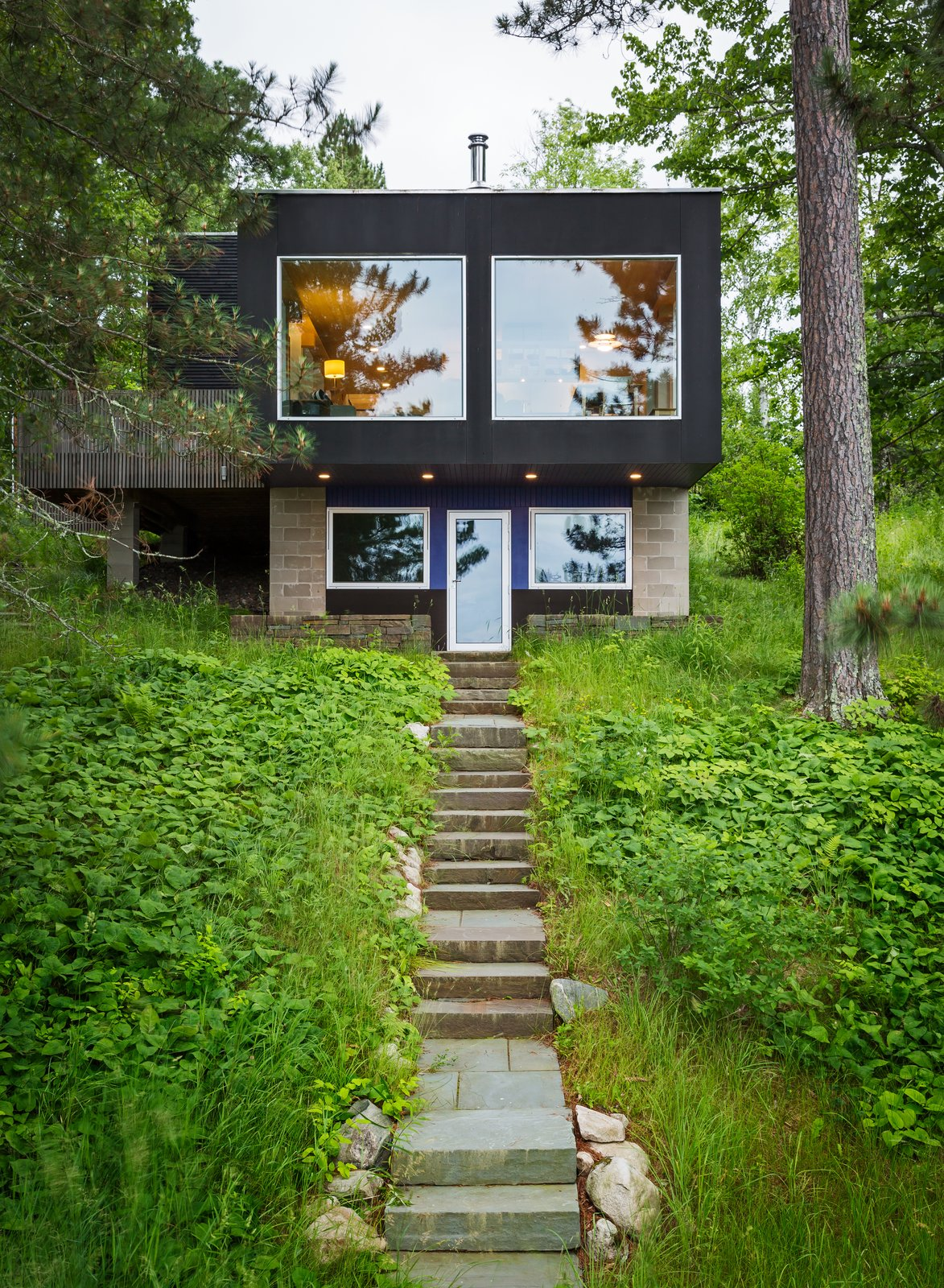 "Staircase and Stone Tread ""The stone walls, steps, and pathways provide a wonderful warmth and contextual appropriateness to the rugged Northern Minnesota setting,"" says founder David Salmela.  Photo 3 of 15 in Two Rectangular Volumes Unite to Form a Colorful Lakeside Cabin"