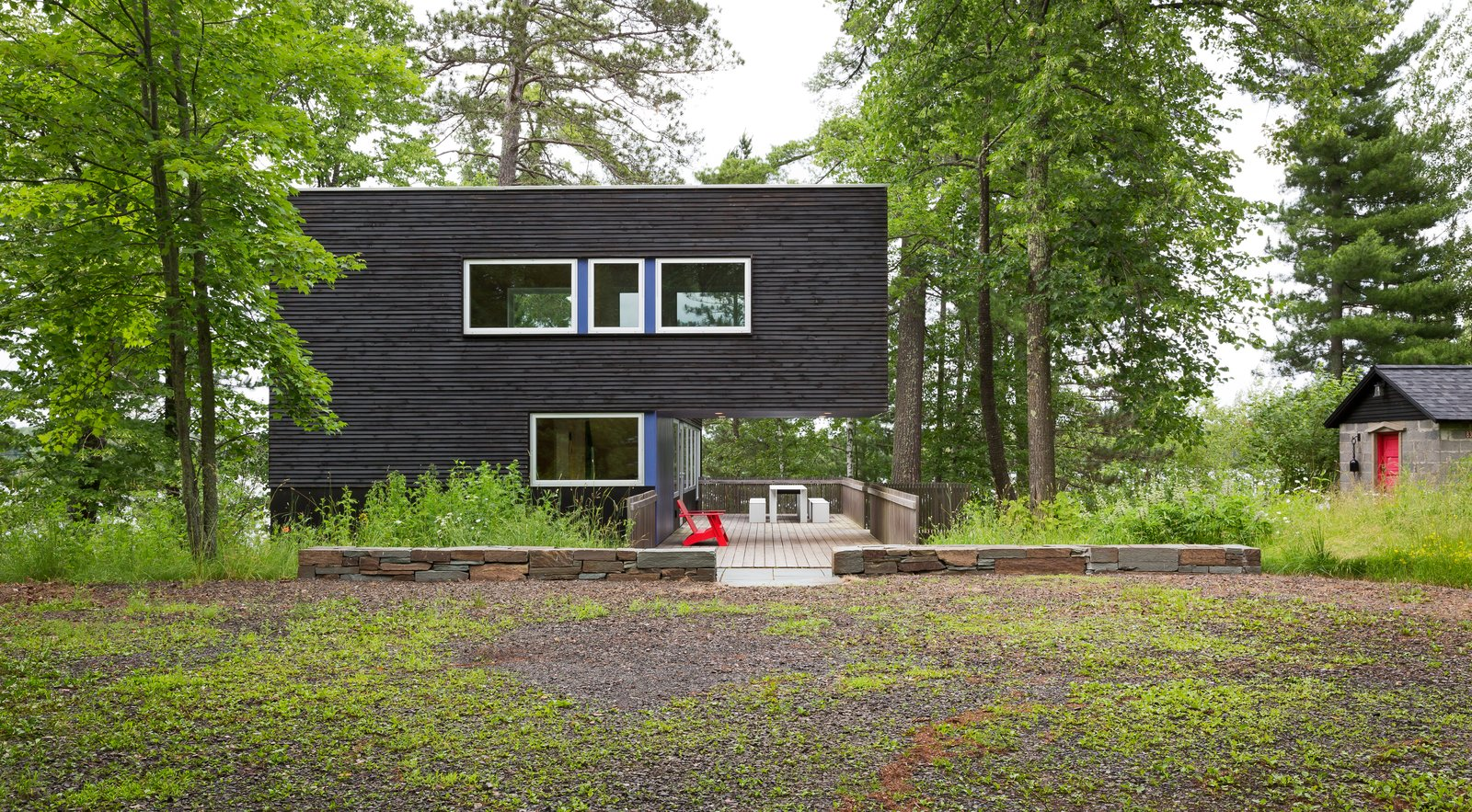 Exterior, Wood Siding Material, Flat RoofLine, and Cabin Building Type The upper volume extends over a small patio.    Best Photos from Two Rectangular Volumes Unite to Form a Colorful Lakeside Cabin