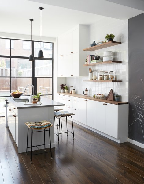 Frederick Tang Architecture renovated this Brooklyn brownstone with entertaining in mind. The new kitchen features a mix of IKEA and custom walnut shelving. The gray subway tile is from Nemo Tile.