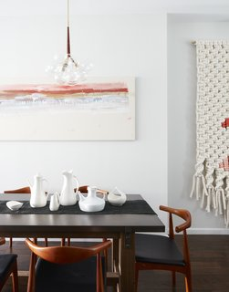 A zinc topped table from Restoration Hardware; lighting fixtures (wrapped in leather) from Pelle; painting on the wall is by Roman painter Giancarlino Benedetti Corcos; large scale wall weaving by Maeve Pacheco; a mix of vintage pottery from Paul McCobb, Ben Seibel, and Eva Zeisel.