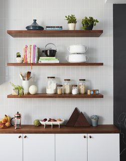 A mix of IKEA and custom walnut shelving; gray subway tile from Nemo Tile; and accessories from Food 52.