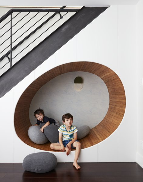 "The space below the stairs was turned into a cheerful play area for the two boys. ""We built an egg shaped 'nook' underneath the staircase, and filled it with soft 'pebble' pillows,"" adds Tang."