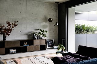 Wood floors and carpet provide a warm contrast to the cool concrete walls.