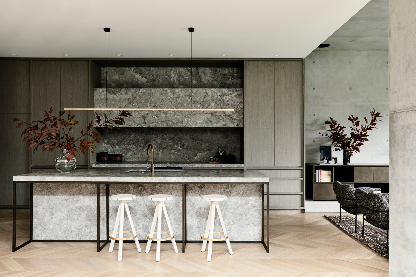 """Kitchen, Marble, Drop In, Pendant, Light Hardwood, and Wood """"A narrative unfolds of stunning detail and tactile material of raw steel, dark paneled walls, concrete, bronze, timber and stone—elements that invite you to touch and feel,"""" says Bear.  Kitchen Drop In Pendant Marble Wood Photos from A Strong Builder Bond Results in a Sophisticated Australian Home"""