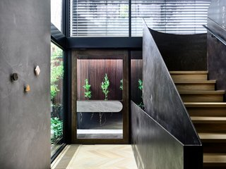 Upon entering the abode, a sculptural, folded-plate staircase immediately catches the eye.