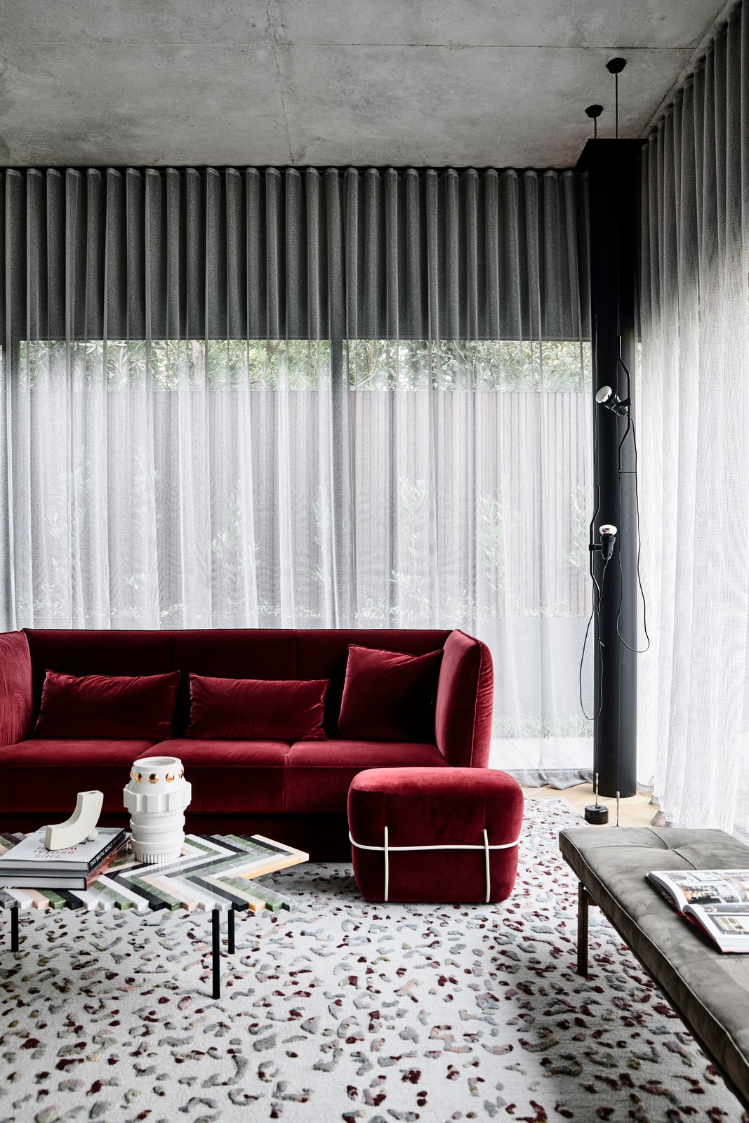 Living Room, Ottomans, Coffee Tables, Bench, Sofa, Ceiling Lighting, Floor Lighting, and Carpet Floor A lavish, velvet-upholstered red sofa in the living room.  Photo 12 of 20 in A Strong Builder Bond Results in a Sophisticated Australian Home