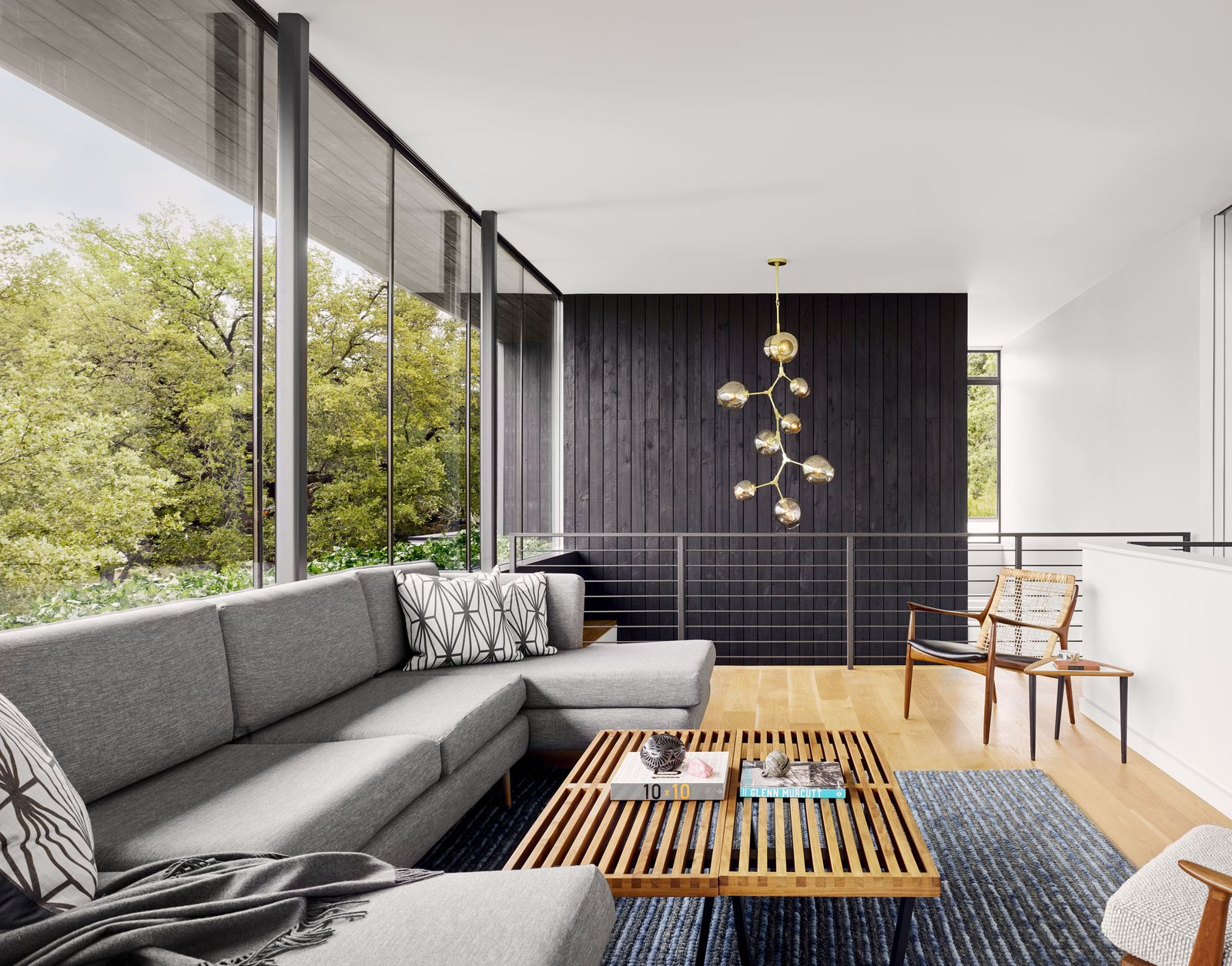 Living Room, Pendant Lighting, Sofa, Coffee Tables, Chair, and Medium Hardwood Floor Wrapped in frameless glass set atop a continuous planter wall, the upper level looks out to the trees and beyond.     Photo 9 of 13 in A Glass Addition Unveils Treetop Views For This Texan Home