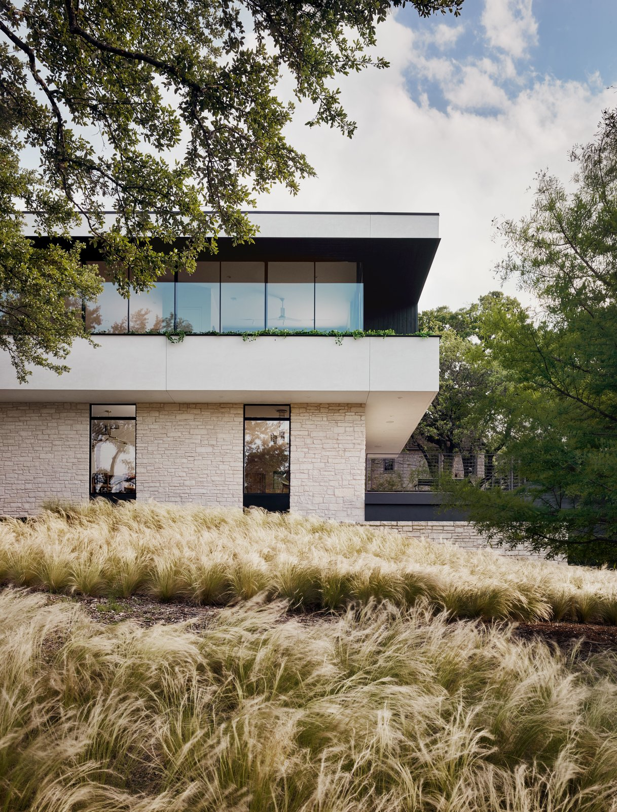 Exterior, Stone Siding Material, Ranch Building Type, House Building Type, Metal Siding Material, Glass Siding Material, and Flat RoofLine  A garage and gym are contained within the lowest level of the house.      from A Glass Addition Unveils Treetop Views For This Texan Home