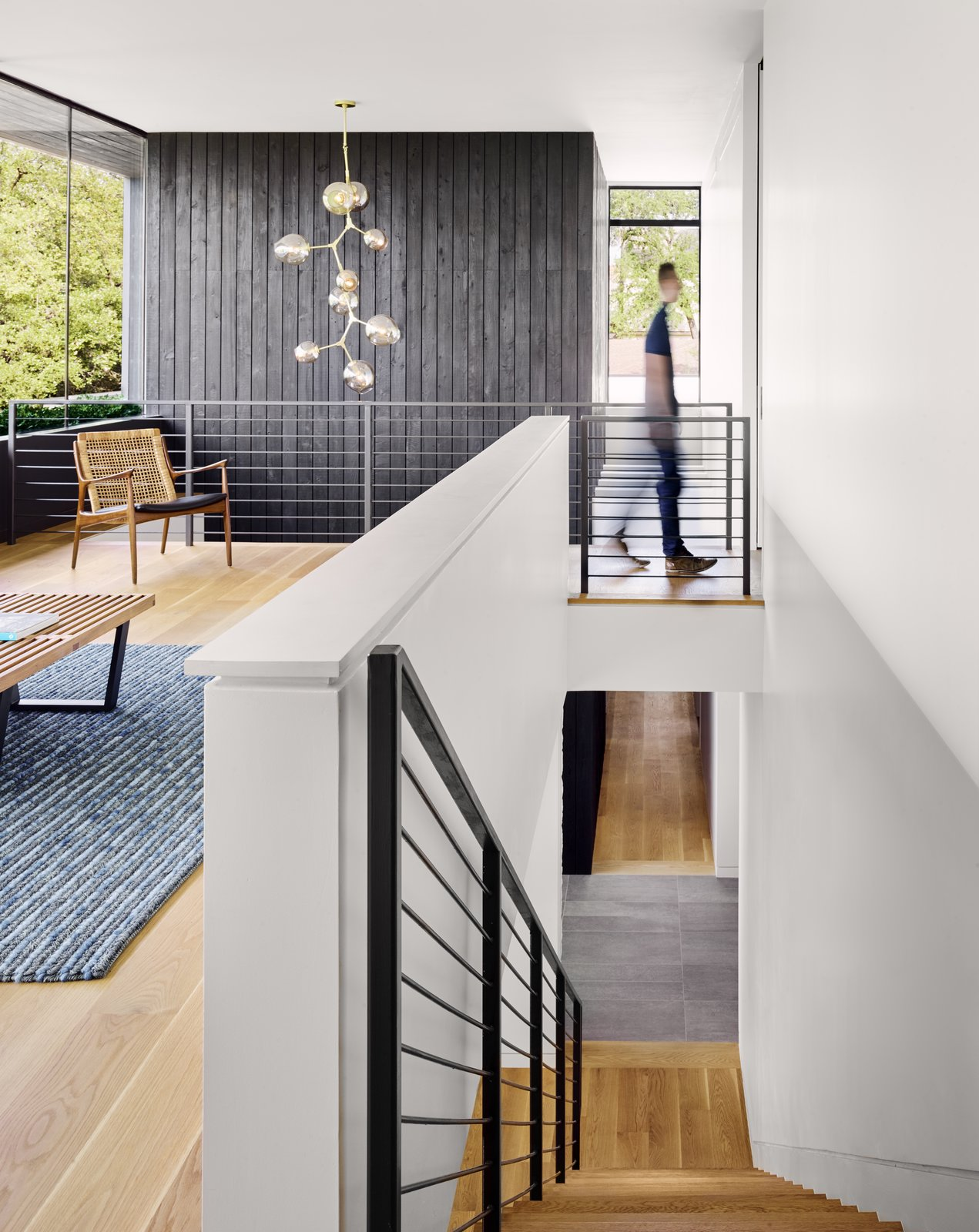 Staircase, Metal Railing, and Wood Tread The large windows open up the interiors by creating double-height spaces that draw natural light into the heart of the house.      from A Glass Addition Unveils Treetop Views For This Texan Home