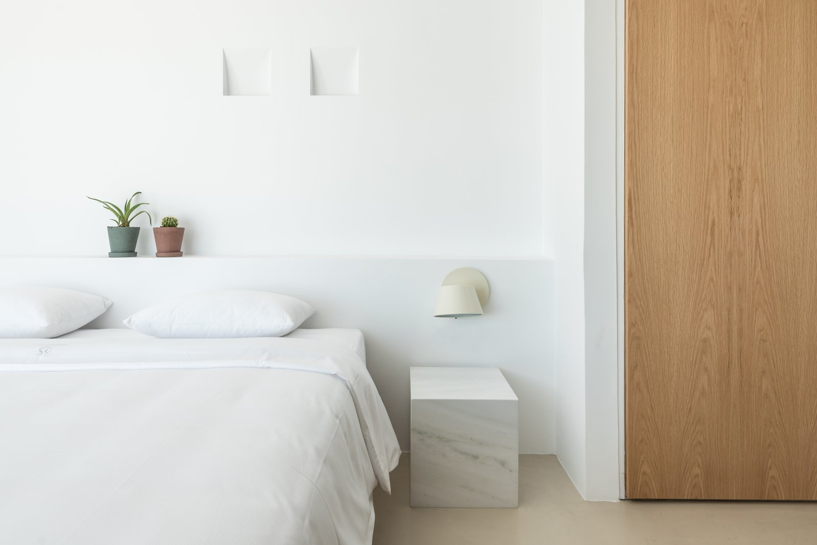 Bedroom, Wall, Night Stands, Bed, Accent, and Concrete Warm timber and plants add a touch of softness to the stone and concrete foundation.  Best Bedroom Bed Concrete Wall Night Stands Photos from A Modern Home Is Gently Slotted Into a Steep Slope in Santorini