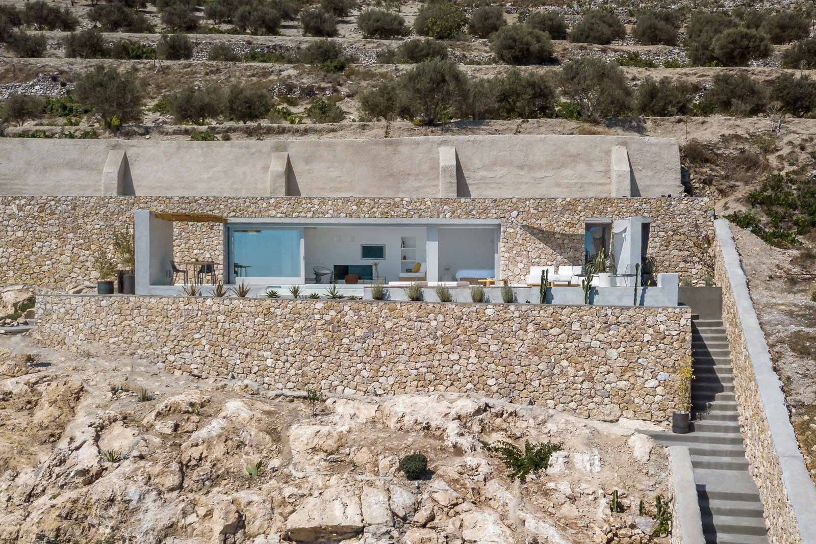 Exterior, Stone, House, and Flat The elongated, rectangular form has been delicately nestled into the island's steep terrain.   Best Exterior Photos from A Modern Home Is Gently Slotted Into a Steep Slope in Santorini