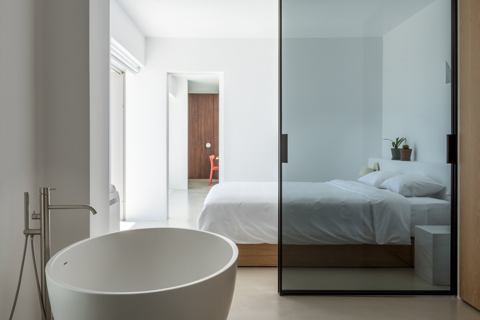 Bedroom, Concrete Floor, Bed, and Accent Lighting Dividers made of brick, wood, and glass separate the different rooms and functional zones.  Photo 14 of 18 in A Modern Home Is Gently Slotted Into a Steep Slope in Santorini