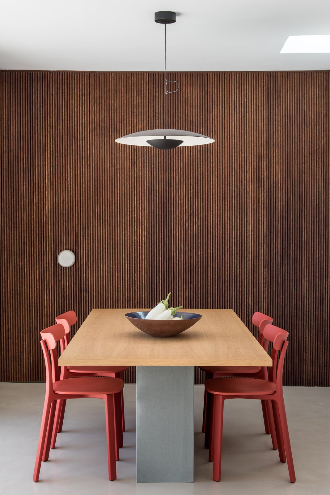 Dining Room, Pendant Lighting, Concrete Floor, Chair, and Table Inside the home, a simple, neutral color scheme harmonizes with warm natural oak, walnut wood, and dramatic black steel details.    Photo 11 of 18 in A Modern Home Is Gently Slotted Into a Steep Slope in Santorini