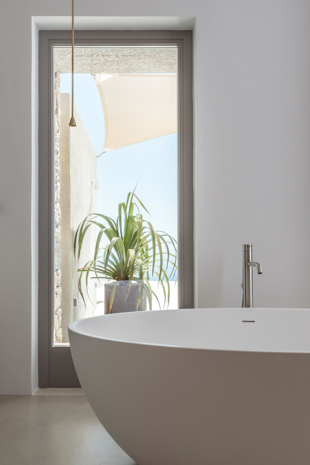 Bath, Freestanding, Soaking, Pendant, and Concrete This bathtub looks out to the outdoor terrace.  Best Bath Soaking Pendant Freestanding Photos from A Modern Home Is Gently Slotted Into a Steep Slope in Santorini