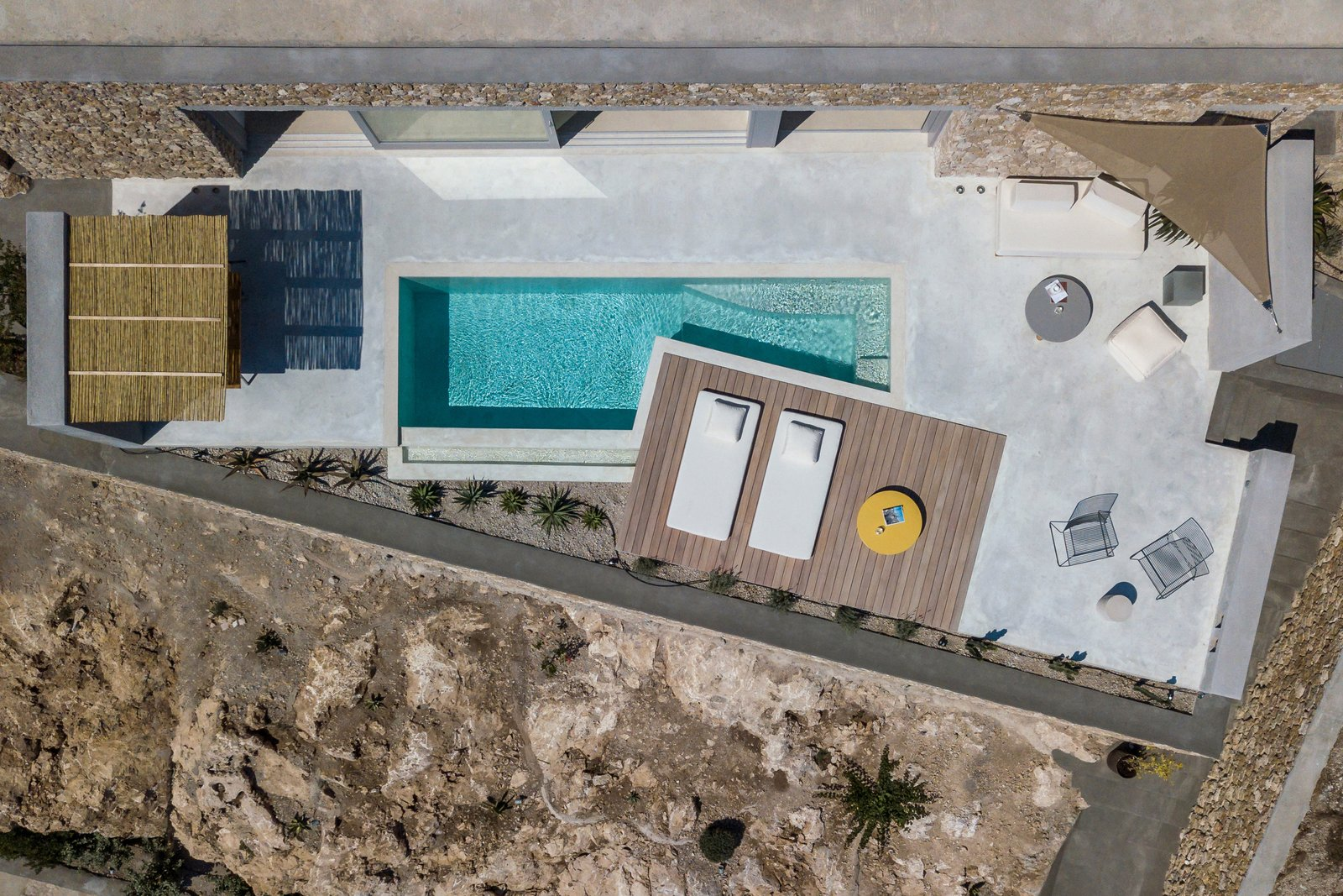 Outdoor, Small, Front Yard, Large, Wood, Concrete, Stone, Decking, Concrete, Concrete, Swimming, and Infinity The excavated material has been used to shape the property's exterior features.  Best Outdoor Small Infinity Photos from A Modern Home Is Gently Slotted Into a Steep Slope in Santorini